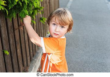 Adorable little boy playing in a neighborhood