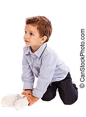 Adorable little boy playing with his toy bear on the floor...