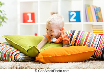 Adorable little boy playing with pillows on floor in children room