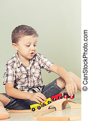 Adorable little boy playing with toys lying on the floor.