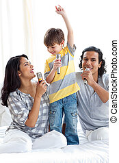 Adorable little boy singing with his parents