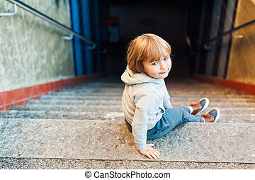 Adorable little boy sitting on steps in a city