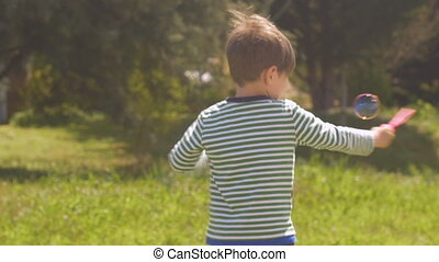Adorable little boy spinning in circles making bubbles in...