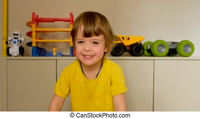 Adorable little boy child speaks and laughs on camera against of his toys in room background