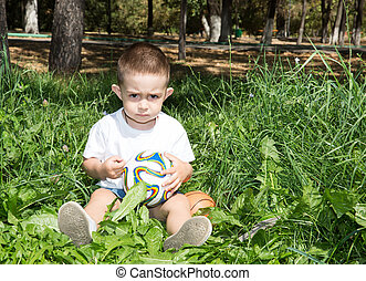 Adorable little child boy with soccer ball in park on nature at summer. Use it for baby, parenting or love concept