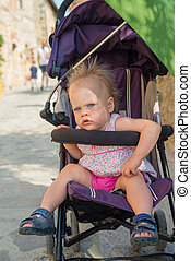 Adorable little child girl in a stroller