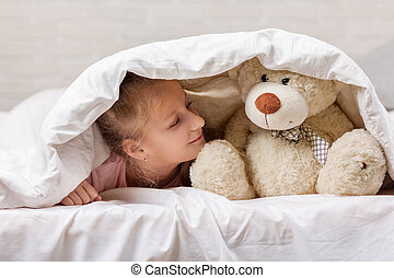 little child girl playing with teddy bear