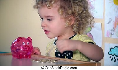Adorable little child saving money in a piggy bank