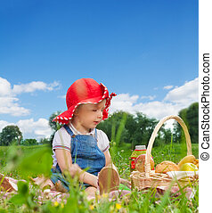 child sitting with picnic basket