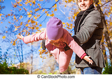 Adorable little girl and happy father having fun in autumn park on a sunny day