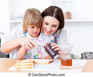 Adorable little girl and her mother preparing toasts