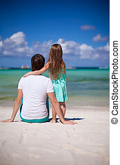 Adorable little girl and young dad at tropical beach