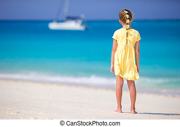 Adorable little girl at beach with flowers in hair on the beach