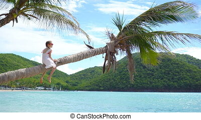 Adorable little girl at tropical beach sitting on palm tree...