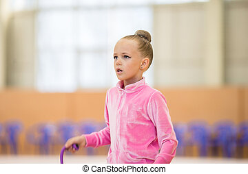 Adorable little girl athletes train in rhythmic gymnastics hall