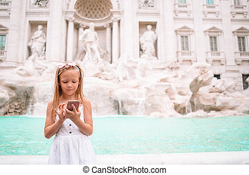 Adorable little girl background Trevi Fountain, Rome, Italy. Happy kid enjoy italian vacation holiday in Europe.