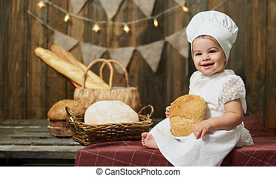Adorable little girl baker with fresh bread on the background of a wooden wall and bread