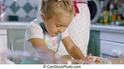 Adorable little girl baking a tart with her mother