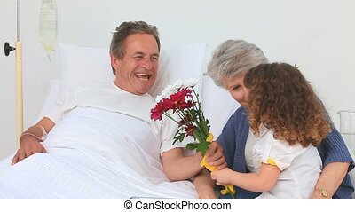 Adorable little girl bringing a bunch of flowers to her sick grandfather
