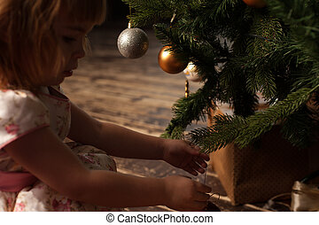 Adorable little girl decorating Christmas tree