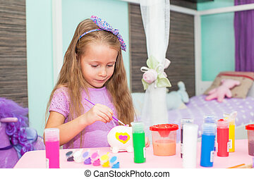 Adorable Little girl draws paints at her table in the room