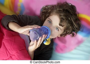 Adorable little girl drinking bottle