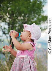 Adorable little girl drinking from bottle outdoor