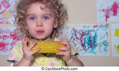 adorable little girl eating a boiled corn on cob. Handheld...