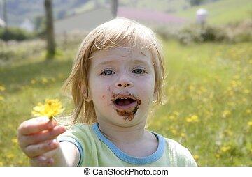 Adorable little girl eating chocolate