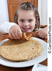 adorable little girl eating crepes