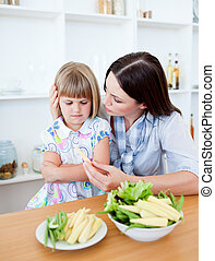 Adorable little girl eating vegetables with her mother in the kitchen