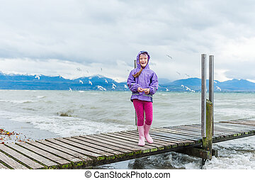 Adorable little girl feeding birds by the lake on a very windy day
