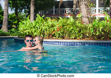Adorable little girl have fun with father in the pool