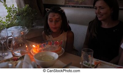 Adorable little girl having birthday party at home, blowing...