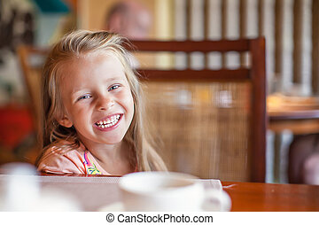 Adorable little girl having breakfast at resort restaurant...