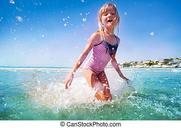 Adorable little girl having fun at shallow water