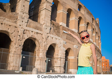 Adorable little girl having fun background of Colosseum in Rome, Italy.