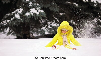 Adorable little girl having fun on winter day outdoors and playing snowballs