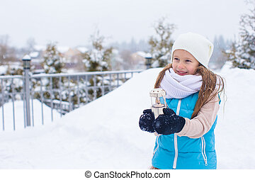 Adorable little girl holding Christmas lantern outdoors on beautiful winter snow day