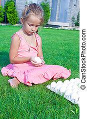 Adorable little girl holding Easter egg sitting on green grass