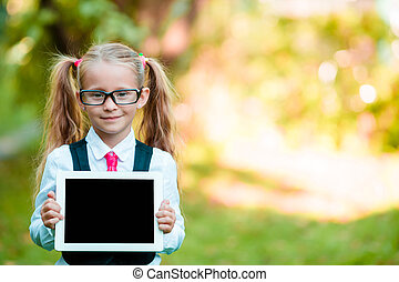 Adorable little girl holding tablet PC outdoors in autumn sunny day