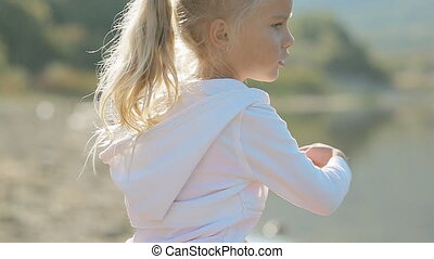 Adorable little girl in bright pink skirt throwing stones...