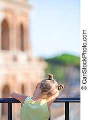 Adorable little girl in front of Colosseum in Rome, Italy. Kid spending childhood in Europe