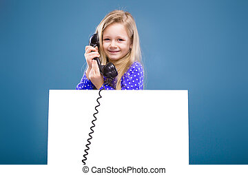 Adorable little girl in purple dress holds empty poster and phone handset
