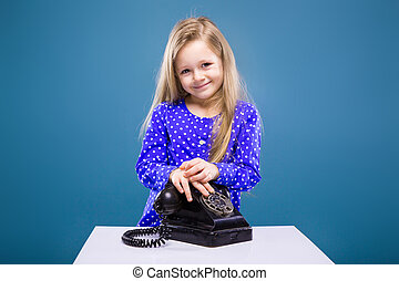 Adorable little girl in purple dress holds phone handset