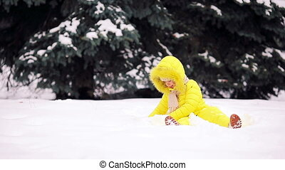 Adorable little girl in snow on winter day outdoors