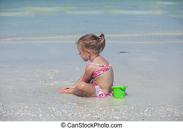 Adorable little girl in swimsuit playing at tropical beach