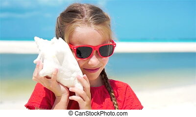 Adorable little girl listening a big seashell on white tropical beach. SLOW MOTION