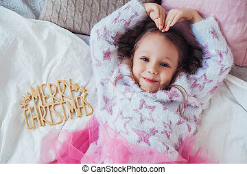 Adorable little girl lying on bed and showing a heart symbol. Golden decoration Merry Christmas.