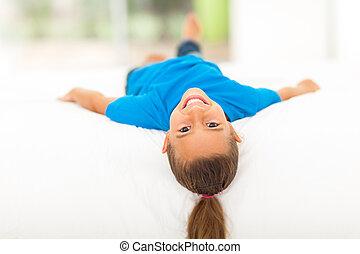 adorable little girl lying on bed